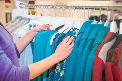 Close up female hands searching through hangers with clothes in store, showroom. Shopping Mall. Shopper. Sales. Shopping Center. S. Elective focus Royalty Free Stock Image