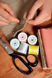 Close-up female hands sewing fabric on old wooden table Stock Images