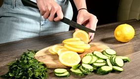 Close-up of female hands slicing a lemon on a stroller on a cutting board next to chopped mint leaves and cucumbers. Healthy and Healthy Vegetarian Food stock footage