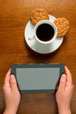 Close-up of female hands with tablet and coffee Stock Image