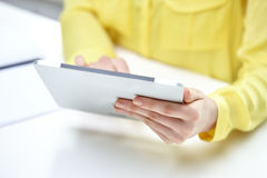 Close up of female hands with tablet pc at table Royalty Free Stock Images