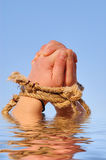 Close up of female hands tied in a rope. On the sea (concept for slave or cast-away theme Royalty Free Stock Images