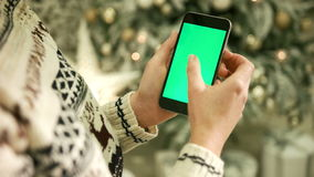 Close-up of female hands touching green screen on mobile phone. Chroma Key. Close up. Tracking motion. Vertical.with. NEW YORK - January 17, 2015: Close-up of stock video footage