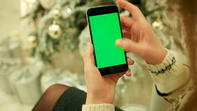Close-up of female hands touching green screen on mobile phone. Chroma Key. Close up. Tracking motion. Vertical.with