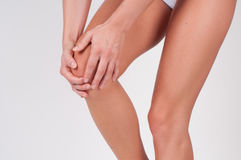 Close-up of female hands touching leg, feeling pain in knee. Suffering from joint pain in her body part Stock Image