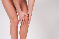 Close-up of female hands touching leg, feeling pain in knee. Suffering from joint pain in her body part Royalty Free Stock Photo