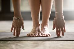 Close up of female hands touching yoga mat. Close up of female hands touching mat, woman practicing yoga at home concept, uttanasana, head to knees, standing stock images