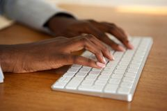 Close up female hands typing on computer keyboard. Close up african american female hands typing on computer keyboard royalty free stock photos