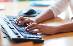 Close up of female hands typing on keyboard. Business, education, programming, people and technology concept - close up of african american female hands typing royalty free stock image