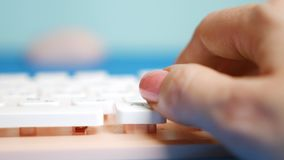 Close-up. Female hands are typing on a pink keyboard, on a blue background. royalty free stock photos