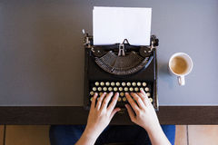 Close up of female hands typing on retro typewriter. Cup of coffee is at right side.Indoors. Top view. Close up of female hands typing on retro typewriter. Cup stock photos
