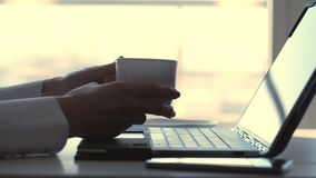 Close-up, female hands typing something on a laptop keyboard. at the same time, a business lady drinks her coffee from a stock footage