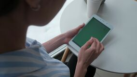 Female using digital tablet. Close up - Female hands using digital tablet with green screen, sitting in cafe stock footage