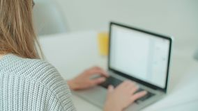 Close up of female hands using laptop computer while sitting at table. Young blonde woman using laptop computer while sitting at table stock footage