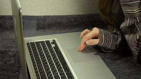 Close up of female hands using laptop lying on the floor at home, slow motion stock video
