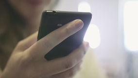 Close up of female hands using a mobile cell phone, indoors. stock footage