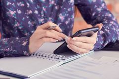 Close-up of female hands using smart phone while working on computer at modern office interior, businesswoman typing royalty free stock image