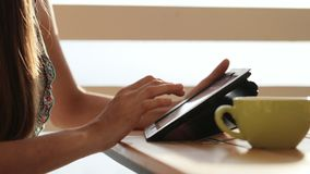 Close-up female hands using tablet in open air cafe. Woman in restaurant with tablet, hot beverage, fruits and croissant in warm sunrise light stock footage