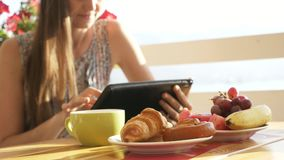 Close-up female hands using tablet in open air cafe. stock footage