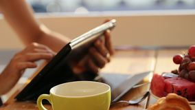 Close-up female hands using tablet in open air cafe. Woman in restaurant with tablet, hot beverage, fruits and croissant in warm sunrise light stock video
