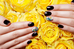 Close Up of Female Hands Wearing Bright Polish on Nails and Holding Yellow Roses stock photography