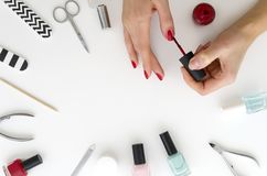 Close up of female hands making manicure with red nail polish.Frame made of manicure equipment on white background. Flat stock photos