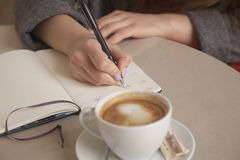 Close-up of female hands. Woman writing plan in notepad. Signing royalty free stock image