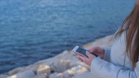Close-up of female hands writing a message on a cell phone. With the sea on a background stock footage