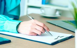 Close-up of female hands writing something in clipboard sitting at office. stock photography