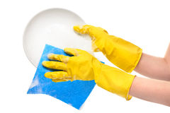 Close up of female hands in yellow protective rubber gloves washing white plate with blue rag Stock Image