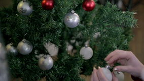 Close up on female hanging Christmas ornaments on tree. Young romantic couple decorating Christmas tree by a fireplace with red and silver ornaments, red, blue stock video