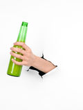 Hand holding a beer bottle through a white paper Stock Photos