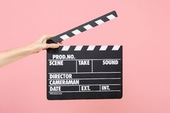 Close up female holding in hand classic director clear empty black film making clapperboard isolated on trending pastel stock photography