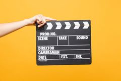 Close up female holding in hand classic director clear empty black film making clapperboard isolated on trending yellow. Close up female holding in hand classic stock photos
