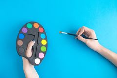 Close up of female holding paint palette and brush isolated on blue. royalty free stock images