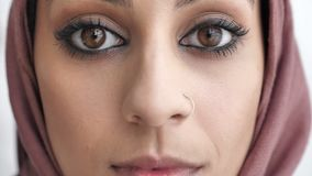 Close-up of female Indian sad eyes. Young beautiful serious Indian girl in pink hijab looking at camera. Portrait, white stock footage