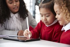 Close up of female infant school teacher sitting at a desk in a classroom helping two schoolgirls wearing school uniforms using a. Tablet computer and stylus royalty free stock images