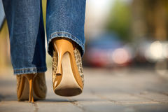 Close-up of female in jaguar spotted shoes walking stock photography