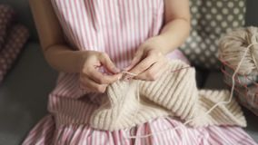 Close up female knitting hands. Woman hobby knitting wool sitting on couch. Woman leisure in home stock footage