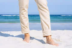 Close-up of female legs in beige pants barefoot on the beach Royalty Free Stock Image