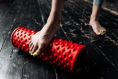 Close-up of female legs. The girl works out her feet with a massage roll. Prevention of flat feet