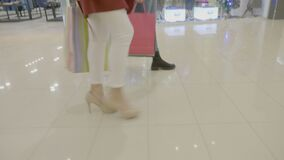 Close up of female legs in heels marching in a fashion way at the mall while carrying shopping bags in their hands -. Close up of female legs in heels marching stock footage