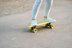 Close-up of female legs in jeans and sneakers riding a skateboar Royalty Free Stock Images