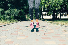 Close-up of female legs in sneakers jumping rope in summer outdo. Ors, low angle shooting, soft focus Stock Image