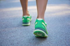 Close up of female legs in sporty shoes running on road Royalty Free Stock Photography