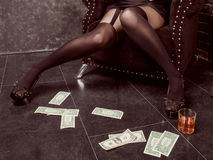 Close-up of female legs in stockings and near them lie on the floor dollar notes and a glass with alcohol Stock Image
