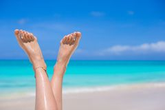 Close up of female legs on white sandy beach Royalty Free Stock Photography