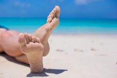 Close up of female legs on white sandy beach Royalty Free Stock Photos