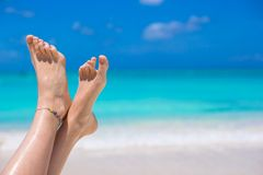 Close up of female legs on white sandy beach Royalty Free Stock Photo