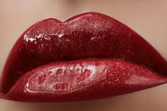 Close-up of female lips with bright makeup. Macro of woman`s face. Fashion lip make-up with red lipgloss Stock Photography